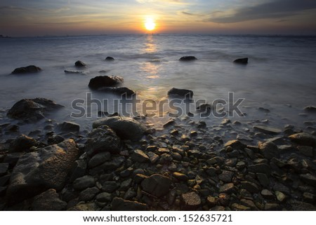 sun set on sea scape with natural rock  foreground - stock photo