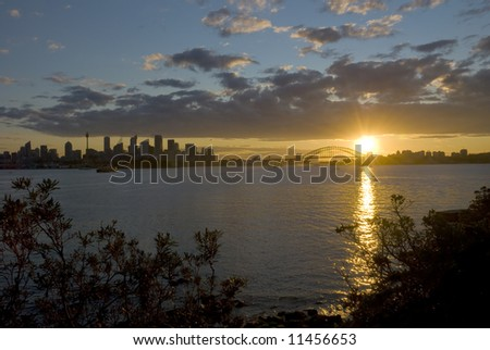 Sun sets behind Sydney Harbour Bridge with city and Sydney Opera House in the distance - stock photo