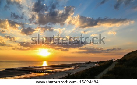 Sun sets down at the sandy Netherlands coast - stock photo