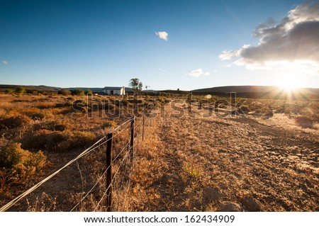 Sun sets over a semi arid desert as a farm fence runs throughout this image. This image contains sunfalre and a sunburst - stock photo