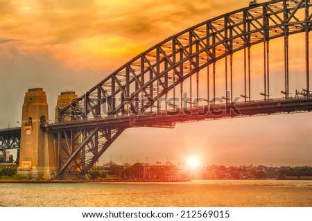 Sun sets over Harbor Bridge in Sydney, Australia - stock photo