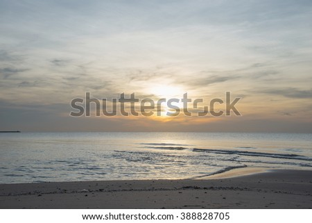 Sun sets over horizon of ocean. Sky, water and shore in the evening painted in orange, gold color. - stock photo
