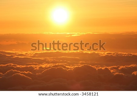 Sun setting above the clouds at 14,000 feet on Mauna Kea,  Hawaii - stock photo