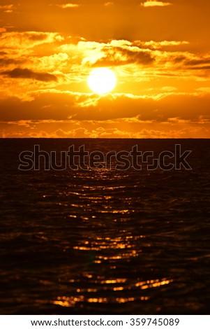 Sun setting above the Pacific Ocean, Kauai, Hawaii - stock photo