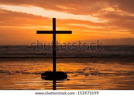 Sun setting behind a cross on a beach. - stock photo