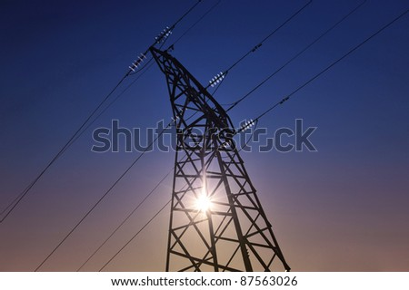 Sun setting behind a  electricity pylons
