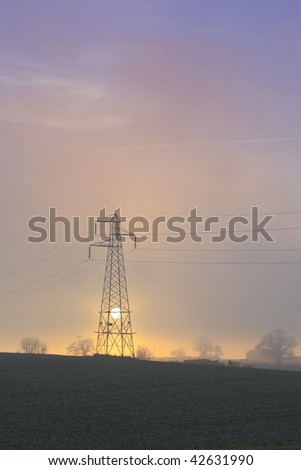 sun setting behind a pylon as the mist rises over the landscape