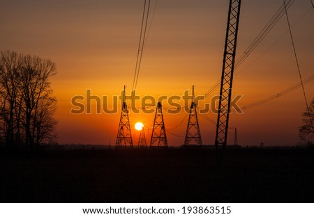 Sun setting behind a row of electricity pylons - stock photo