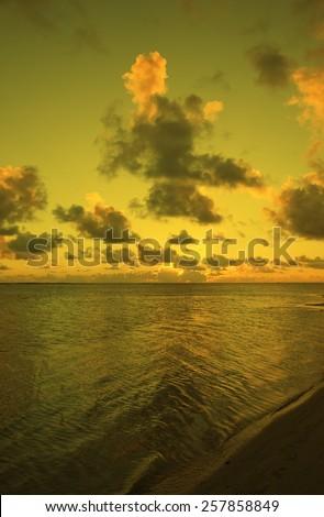 Sun setting behind Cumulus Clouds over Ocean and Island - Rarotonga, Cook Islands, Polynesia - stock photo