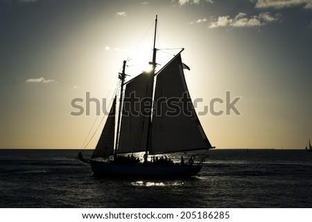 Sun setting behind sailboat - stock photo