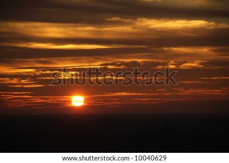 Sun setting in orange sky with clouds.