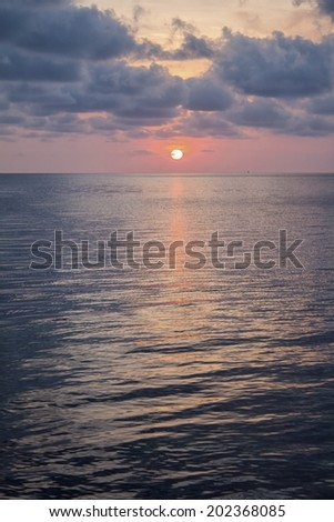 sun setting into the ocean on a cloudy day