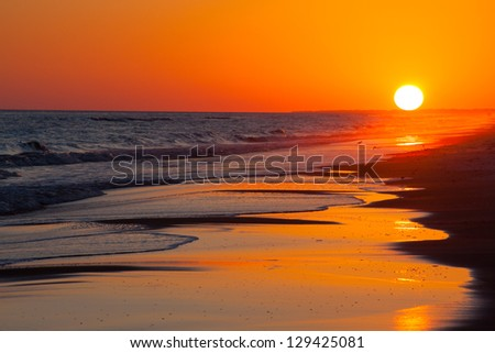 Sun setting on the beach with orange and yellow sky
