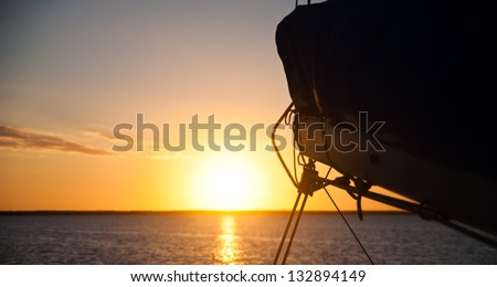 Sun setting over the ocean with the boom and mainsail of a sailboat in the foreground.  copy space available - stock photo