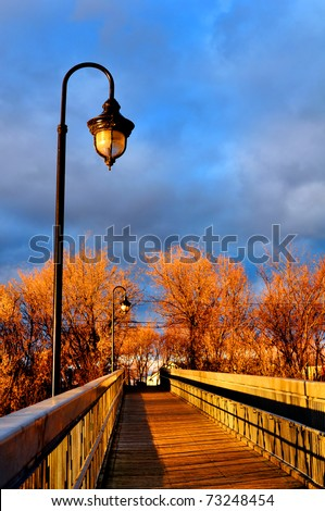 Sun setting over the wooden bridge of a small town on a autumn day. - stock photo