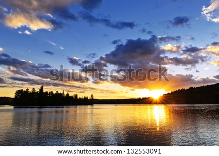 Sun setting over tranquil lake and forest in Algonquin Park, Canada - stock photo