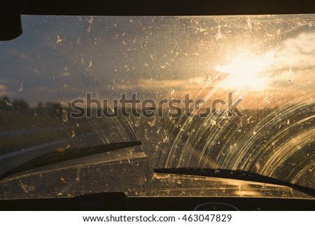 Sun shines at sunset in the glass of  car with dust and insects crashed about him