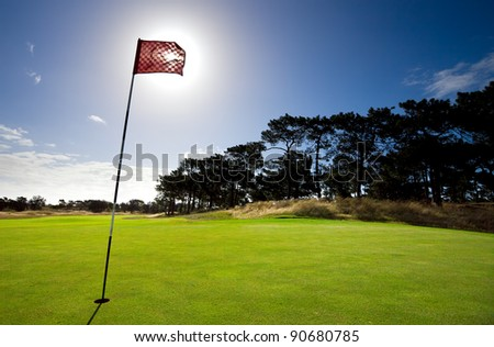 Sun shines behind a golf flag - stock photo