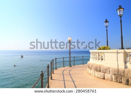 Sun shines on the promenade and calm waters of the Adriatic sea, Opatija, Croatia - stock photo
