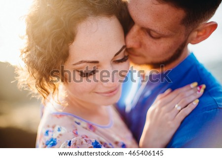 Sun shines through the lady's curls while man embraces her
