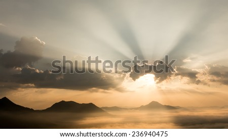 Sun shining behind the clouds on the mountain. - stock photo