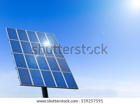 Sun shining in a solar panel against a blue sky - stock photo