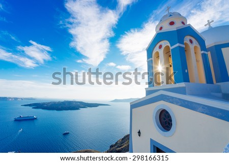 Sun shining through belltower of a church with a view of Santorini volcanic caldera and ships in it, Santorini, Cyclades, Greece - stock photo