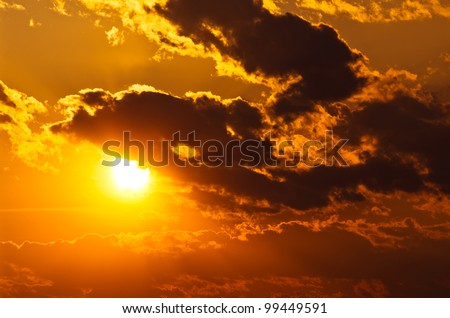 sun shining through clouds at sunset - stock photo