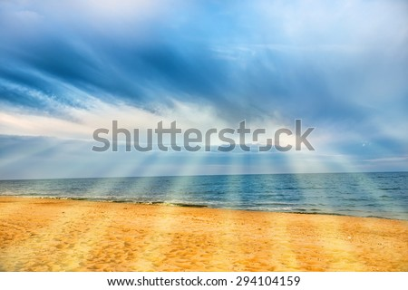 Sun shining through clouds with sunbeams above tropical beach with yellow sand and blue sea - stock photo