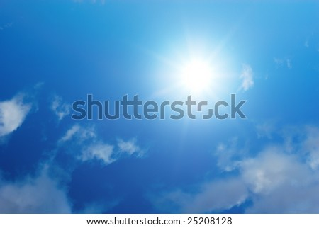 Sun shinning in a blue sky with white clouds