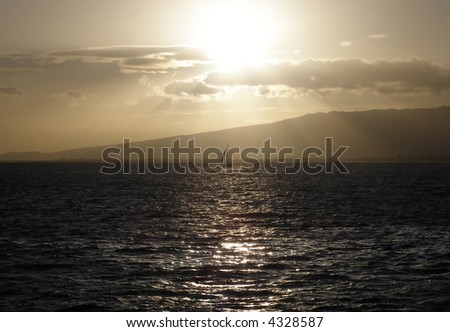 Sun shinning through the clouds in Hawaii over the Pacific Ocean - stock photo