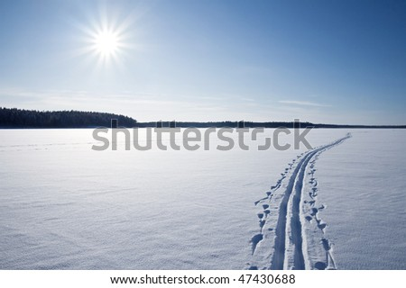 Sun, snow and Ski track crossing a frozen lake. Winter sport - cross-country skiing. - stock photo