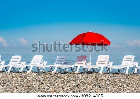 Sun umbrella and beach beds on the shingle beach near sea - stock photo