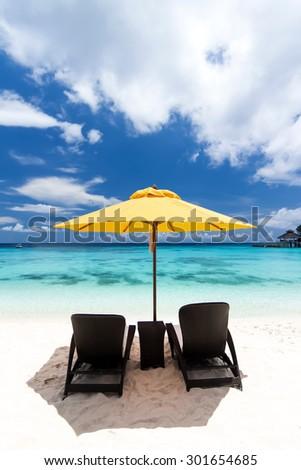 Sun umbrella and beach beds on tropical beach - stock photo