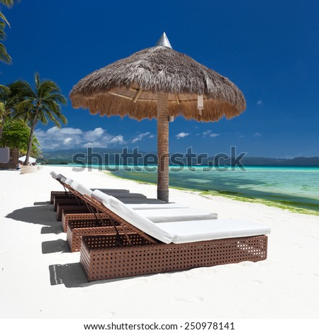 Sun umbrella and beach beds on tropical coastline, Philippines, Boracay  - stock photo