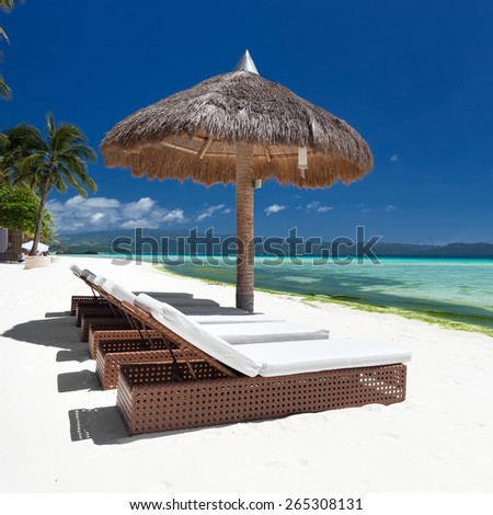 Sun umbrella and beach beds on tropical coastline, Philippines, Boracay