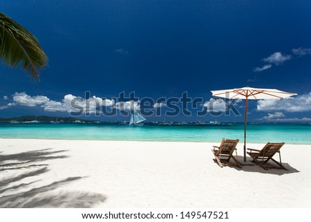 Sun umbrella and beach chairs on tropical beach, Philippines, Boracay - stock photo