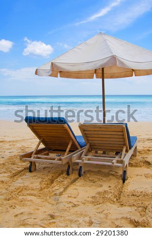 Sun, umbrella and chairs on sandy beach in Bali, Indonesia.