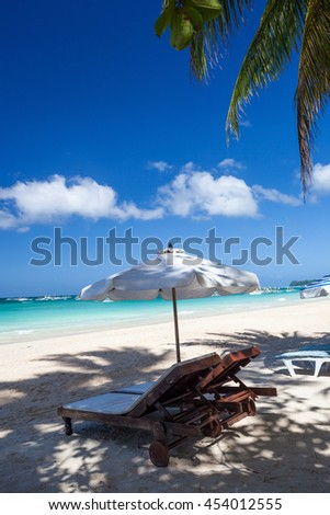 Sun umbrella and sunlongers on sandy tropical beach with white sand and turquoise sea water - stock photo
