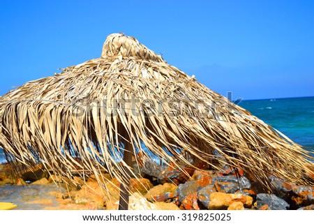 Sun umbrella on the beach in Malia, Crete, Greece. - stock photo