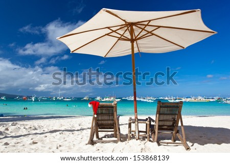 Sun umbrella with Santa Claus Hat on chairs on tropical beach