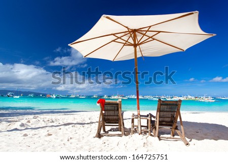 Sun umbrella with Santa Claus Hat on chairs on tropical beach. Christmas card