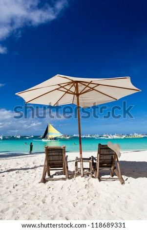 Sun umbrella with Sun Hat on chair - stock photo
