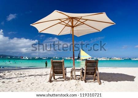 Sun umbrella with Sun Hat on chair longue  on tropical beach - stock photo