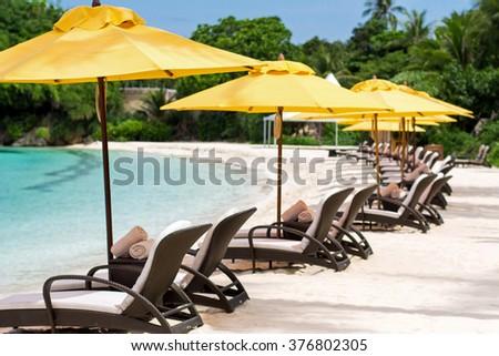 Sun umbrellas and beach chairs on tropical beach, Philippines, Boracay - stock photo