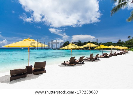 Sun umbrellas and chairs on tropical beach - stock photo