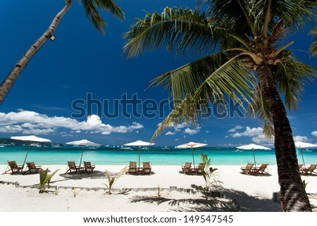 Sun umbrellas and chairs on tropical beach, Philippines, Boracay - stock photo