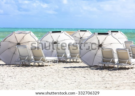 Sun umbrellas on the beach of ocean. Miami Beach, Florida. - stock photo