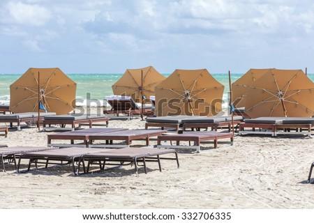 Sun umbrellas on the beach of ocean. Miami Beach, Florida. - stock photo