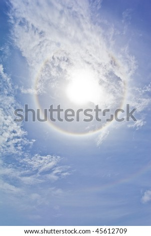 Sun with circular rainbow, clouds and blue sky